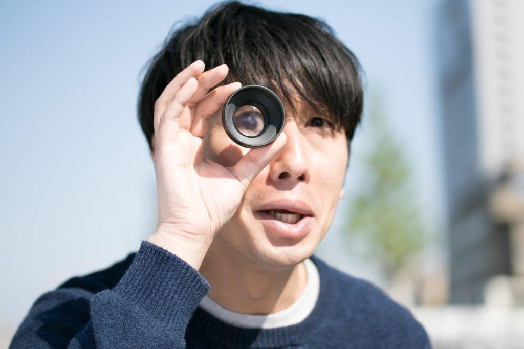 レンズを覗き込む男性