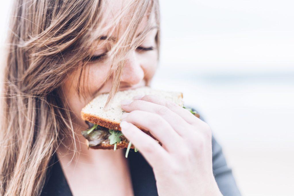 サンドウィッチを食べる女性