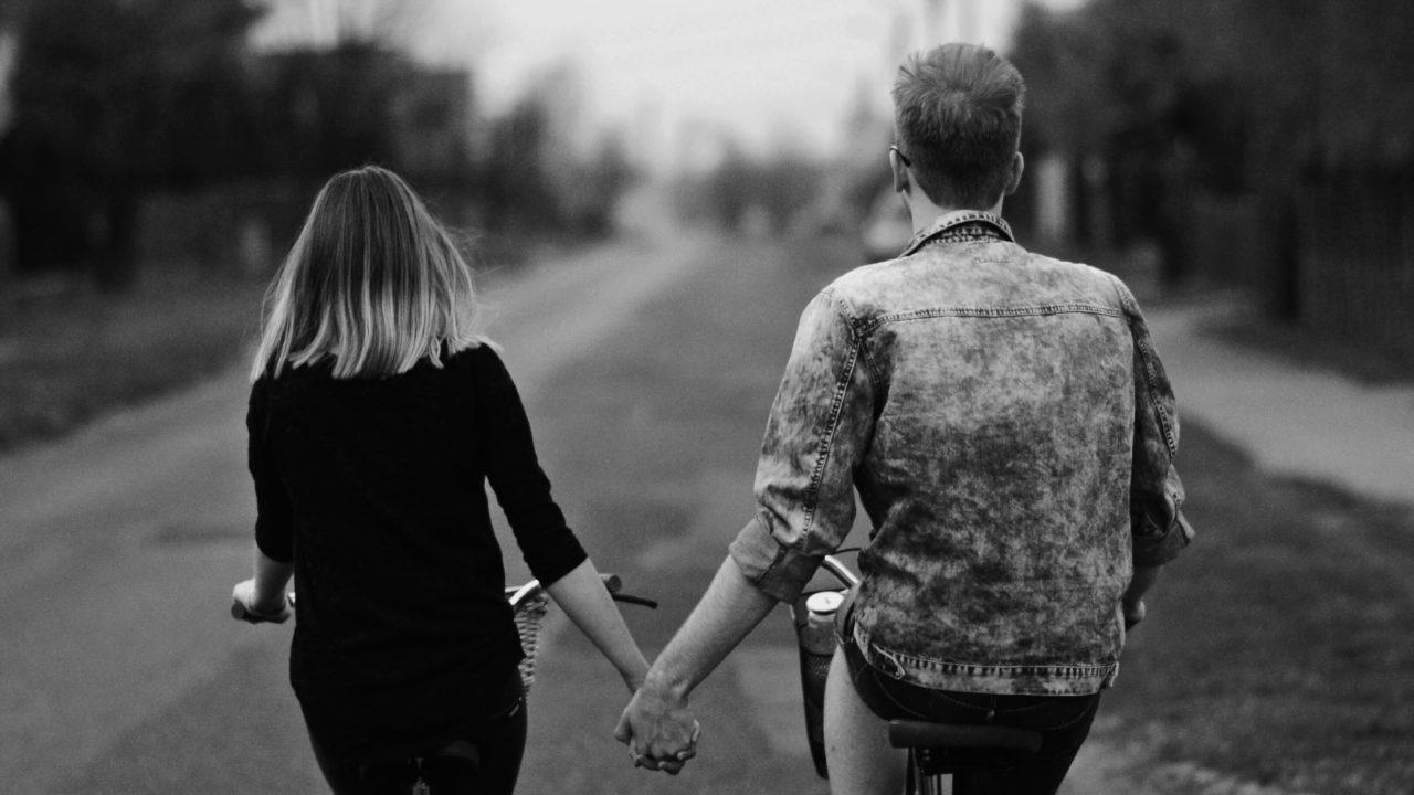 手を繋ぎながら自転車をこぐカップル