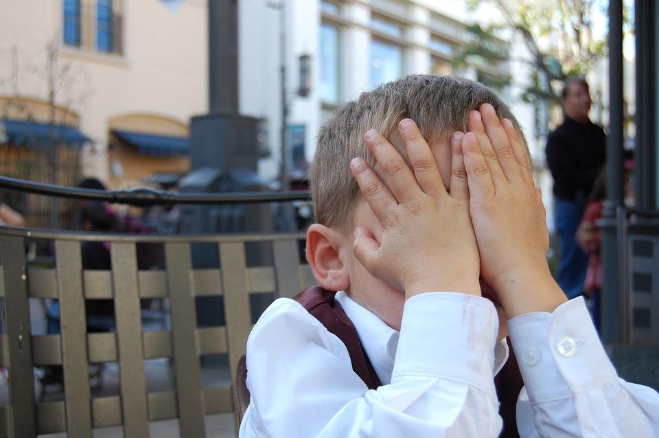顔を隠し嫌がる少年