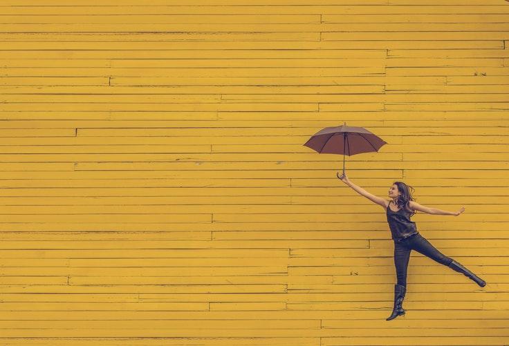 傘を持ち浮かれる女性