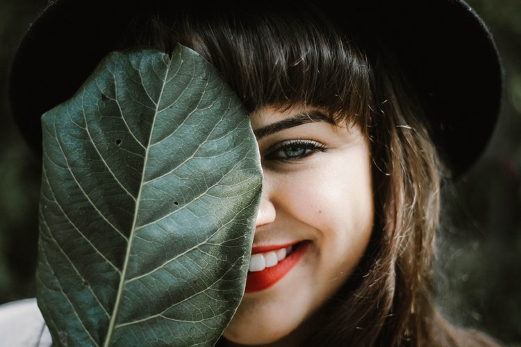 葉っぱで顔の半分を隠す女性