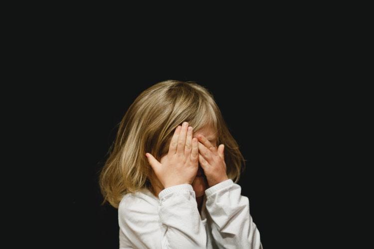顔を隠し恥ずかしがる少女