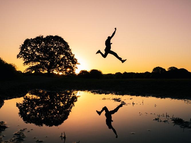 夕日に向かってジャンプする男性