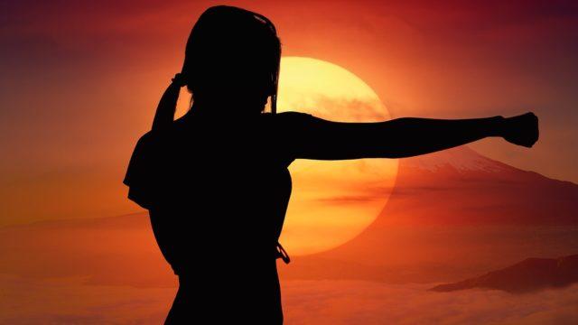 夕日をバックに修行を積む女性