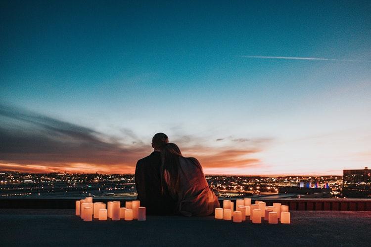 寄り添いながら夕日を眺めるカップル
