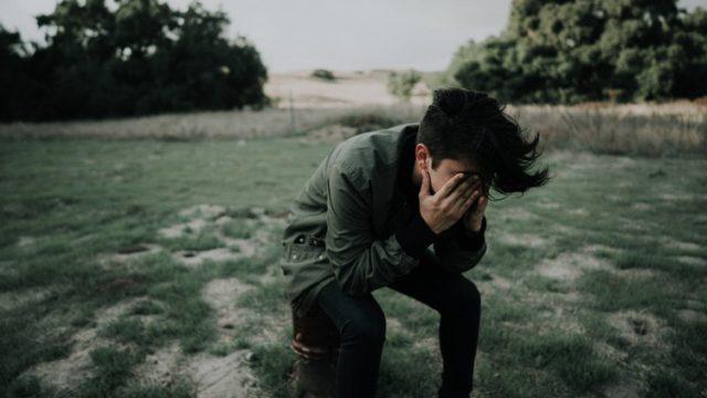 腰をかけ悲しむ男性