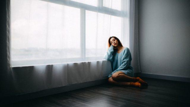 寂しそうに窓にもたれかかる女性