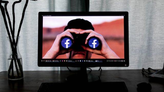 フェイスブックのロゴが印字された双眼鏡を覗く弾性