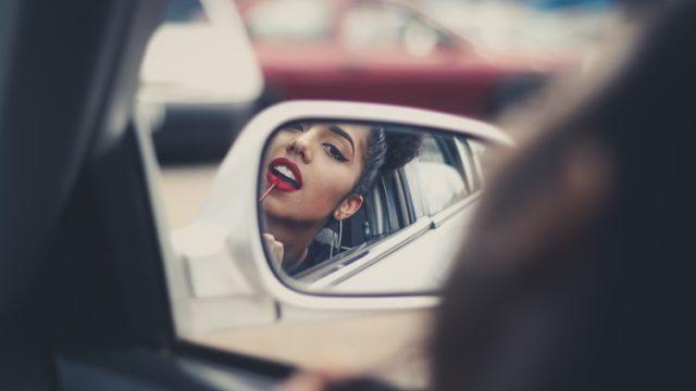 車のミラー越しにこちらを見る女性