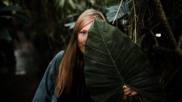 大きな葉で顔を隠す女性