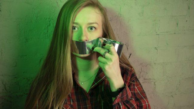 ガムテープで口を覆う女性