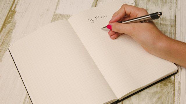 手帳に予定を書く女性
