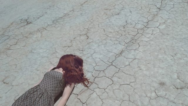 地面に倒れこむ女性