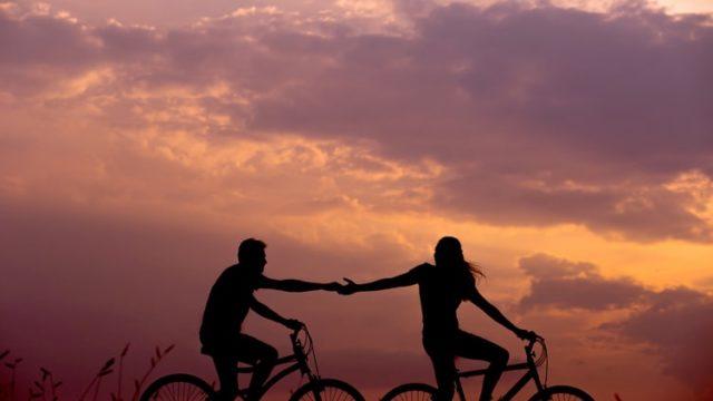 自転車に乗りながら手をつなぐカップル