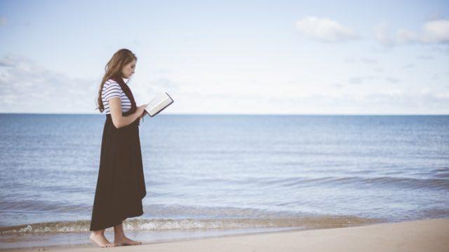 海沿いで読書をする女性