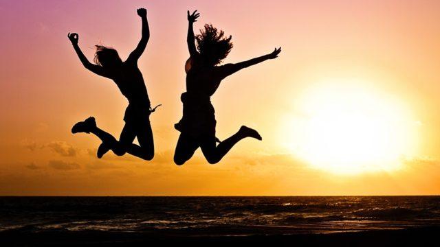 夕日を背にジャンプする女性たち