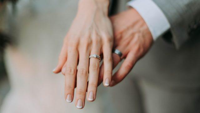結婚指輪をはめた手を重ねる夫婦