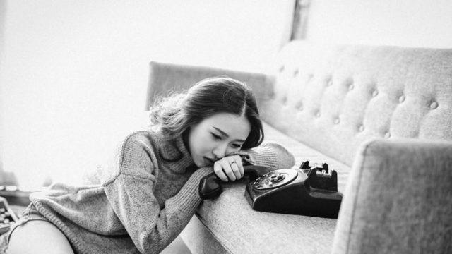 ソファにもたれかかり電話を待つ女性