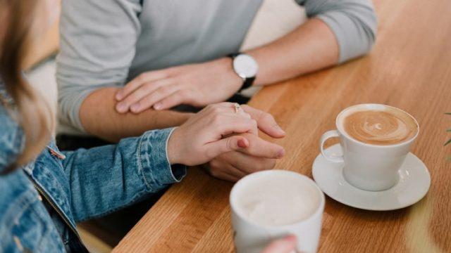 カフェで手を握り合う男女