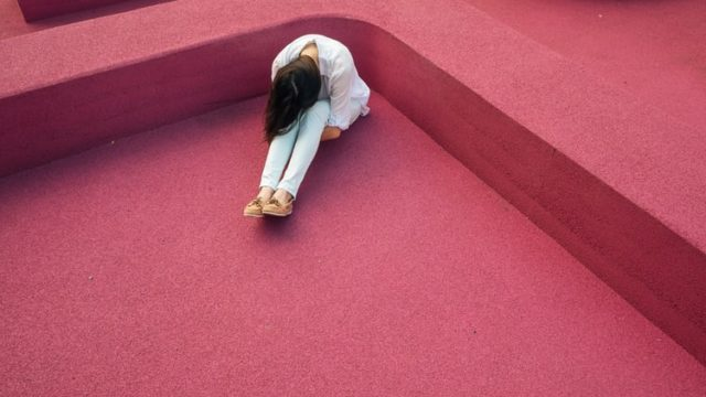 膝を抱えて悲しむ女性
