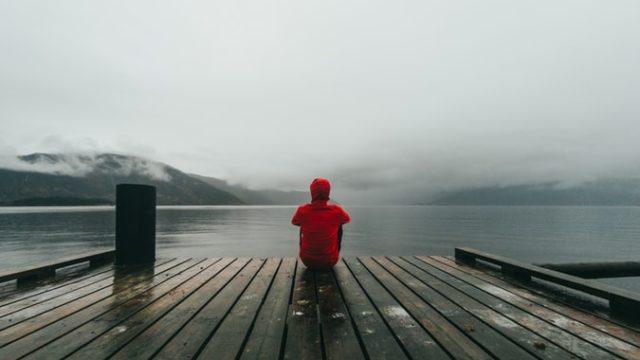海を見つめてうなだれる人