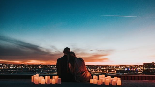 肩を寄せ合い夜景を眺めるカップル